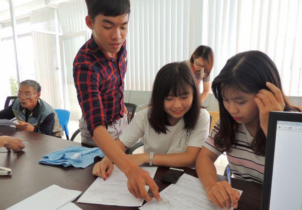 Sinh viên trường Đại học Công nghệ Đồng Nai hướng dẫn cho các em học sinh ghi vào đơn xét tuyển của trường